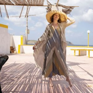 model with raffia hat and handmade linen long dress with stripes and cardigan for woman