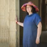 lady with handmade linen summer long dress with sleeves for woman and colorful raffia hat